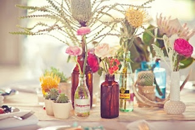 a creative cluster wedding centerpiece of various bottles and vases, blooms, succulents and cacti for a bold look