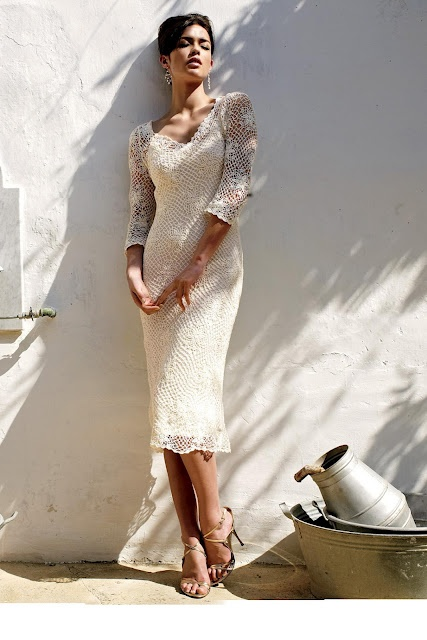 a fitting crochet midi wedding dress with long sleeves and a deep neckline, statement earrings and nude heels for a boho loving bride