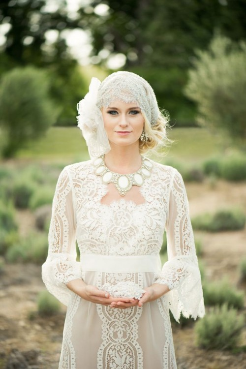 a romantic vintage wedding dress of crochet lace, with long sleeves and a statement necklace plus a cool cap veil with embellishments