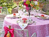 a bright garden bridal shower tablescape with a bold floral centerpiece, colorful linens and bright blooms attached to the chair