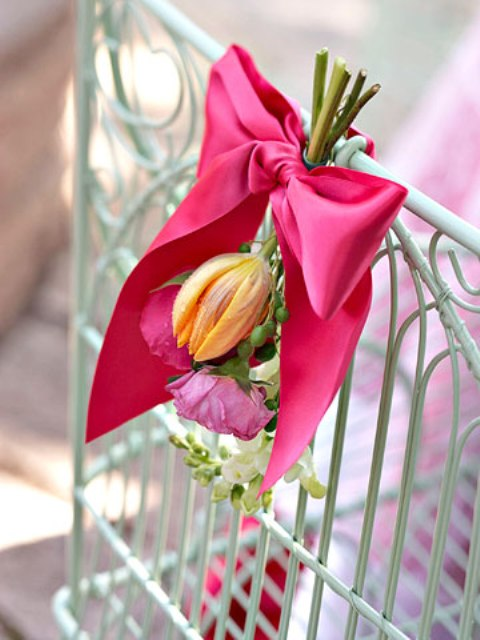 accent your bridal shower chairs with bold blooms and a pink ribbon bow to match your bridal shower theme