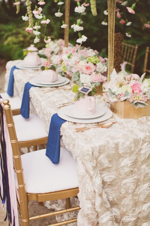 a pretty garden bridal shower table with a fabric flower tablecloth, pretty neutral and pastel florals, fresh blooms hanging from above