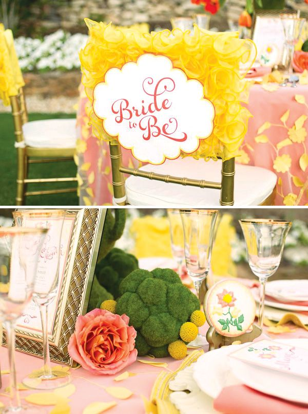 a bright garden bridal shower tablescape with moss balls, craspedia, embroidered blooms, a pink tablecloth with yellow petals