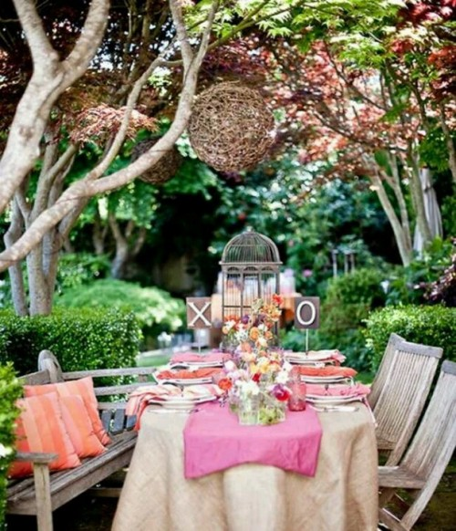 a bright garden shower tablescape with a pink runner, coral and orange napkins, bright blooms, a cage and a vine sphere over the table