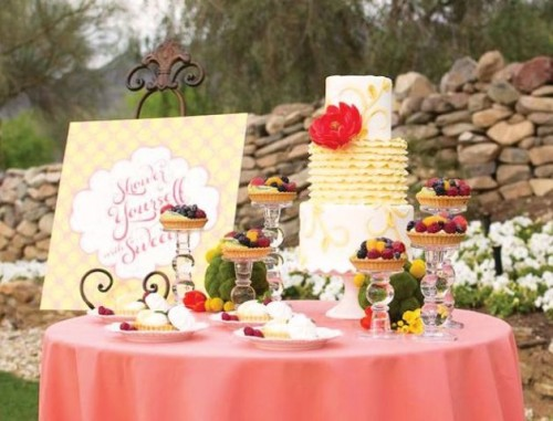 a lovely sweets table with moss balls and craspedia, tarts with fresh berries and a bright yellow cake for a garden bridal shower