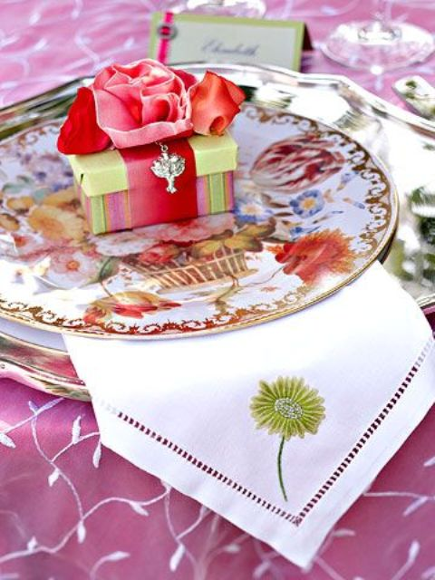 bright floral plates, a neutral napkin with an embroidered flower and a favor box in bold colors
