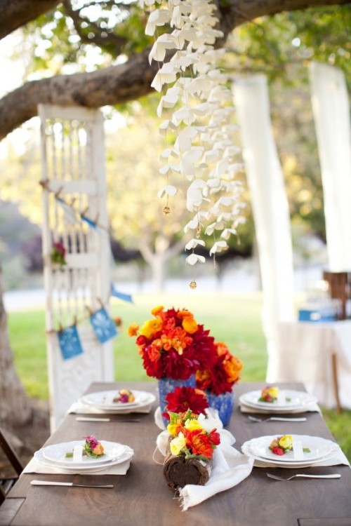 a simple garden bridal shower tablescape with bold florals in blue vases and bold blooms on each place setting plus paper flowers over the table