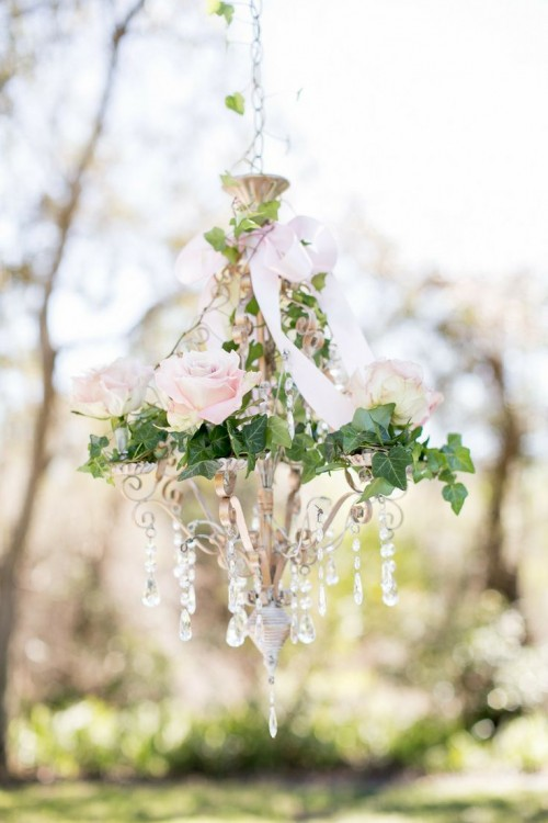a refined crystal chandelier with blush roses and foliage plus a blush bow is a romantic and chic idea for a garden bridal shower