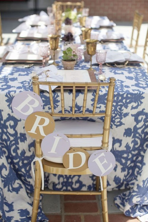 a stylish blue and white wedding tablescape with a printed tablecloth, gold goblets, neutral napkins and a banner on gilded chairs