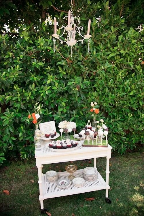 a small white cart with sweets, cake pops and a crystal chandelier over it