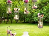 a sweets table with pink blooms and candle lanterns decorated with blooms over it and with delicious sweets and pink champagne