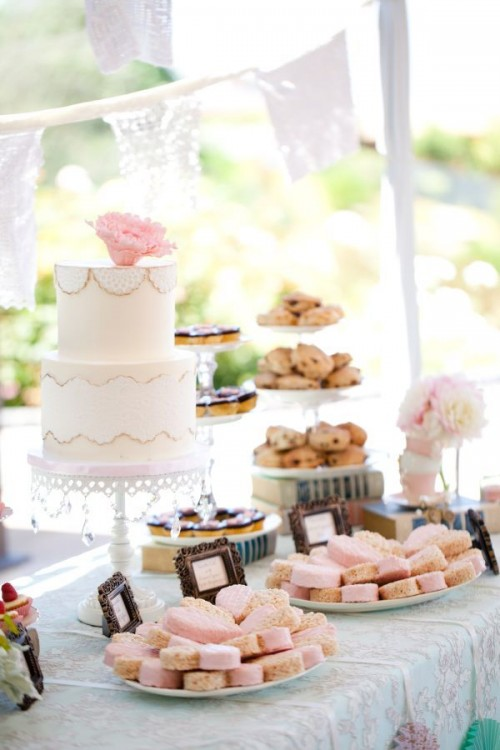 a garden bridal shower sweets table with lots of sweets, a refined neutral cake and some blooms plus a doily garland over the table