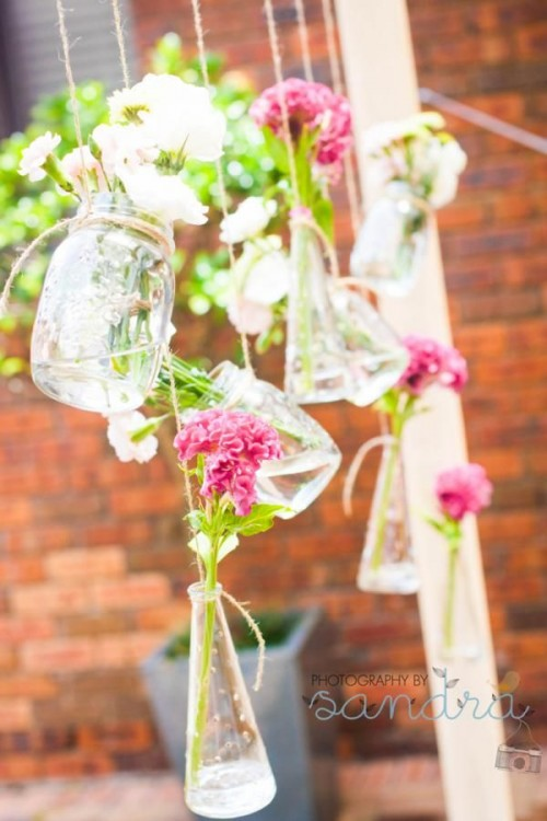 bright and pastel blooms in jars and bottles hanging over the space feels very relaxed and garden-like