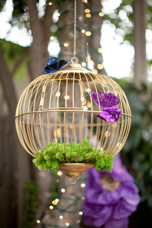 a decorative round cage with moss and paper butterflies for accenting a garden bridal shower space
