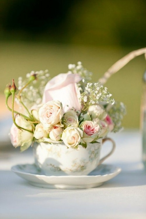 a floral teacup with a saucepan and some neutral and pastel blooms and baby's breath for a refined garden bridal shower