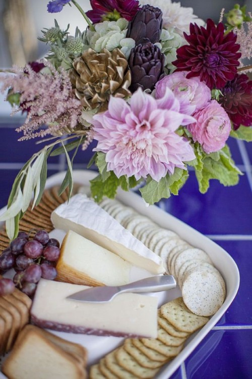 a lovely bold floral arrangement with pink, burgundy and purple blooms and a cheese board is a stylish idea for a garden bridal shower