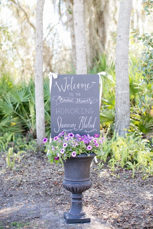 a large vintage urn with purple and pink blooms and a chalkboard sign for a vintage garden bridal shower