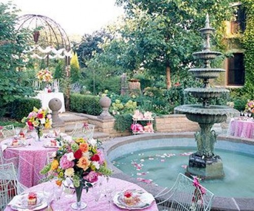 a refined vintage garden bridal shower space with pink tablescapes, bright blooms, petals in the fountain and chic chairs