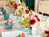 a colorful bridal shower tablescape with bright blooms, pink chargers and turquoise boxes with favors