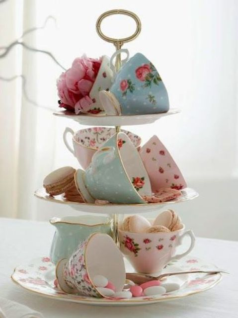 a fun spring bridal shower decoration - a stand with vintage cups, macarons, candies and blooms