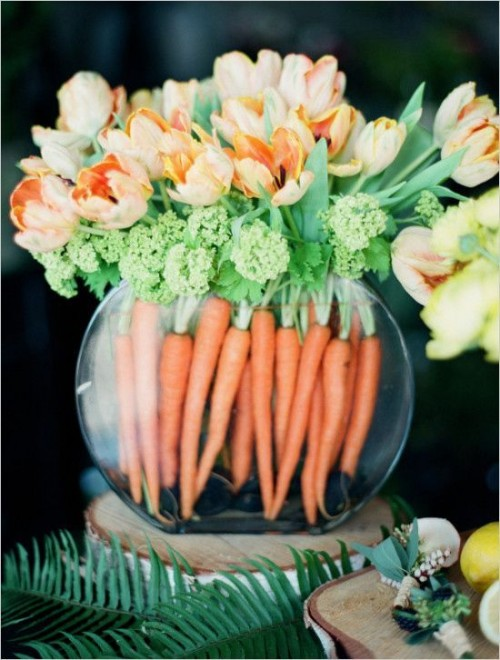a round jar with orange tulips and fresh greenery and fresh carrots to decorate the jar inside