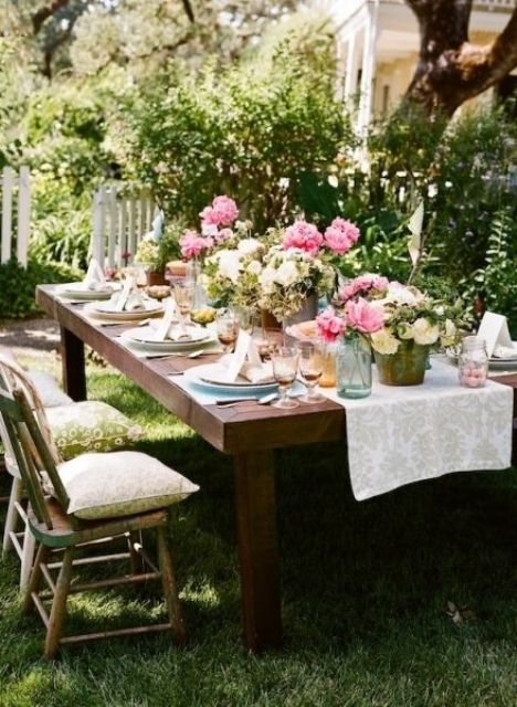 a bright spring bridal shower table with pink blooms, greenery, colored glasses and chargers