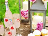 a spring bridal shower dessert bar with pink lemonade, cupcakes and lanterns with blooms inside