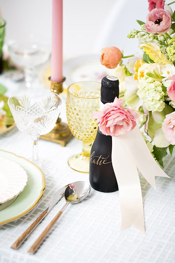 a soft pastel spring bridal shower table with bright blooms, candles and glasses and gold rim plates