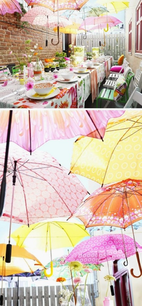a colorful backyard bridal shower with bright umbrellas over the table, floral linens, colorful tableware and bright pillows