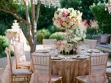 an elegant pink spring bridal shower space with a chic crystal chandelier, pink linens, candles and pastel and white flowers