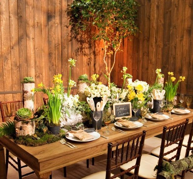 a woodland bridal shower table with succulents, greenery, blooming bulbs, moss and chalkboard signs