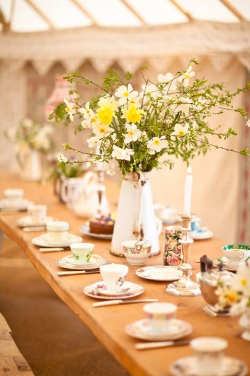 a spring tea party bridal shower table with vintage floral teacups and lush floral centerpieces