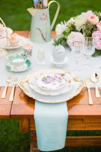 a pastel spring bridal shower table with mint linens, floral tableware, pastel blooms and greenery