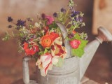 a simple bridal shower centerpiece of a vintage watering can and colorful blooms for decor