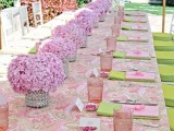 a pastel spring bridal shower table with printed linens, pink blooms and glasses plus green napkins