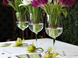 a quirky card table with purple and white tulips in tall glasses for a spring bridal shower