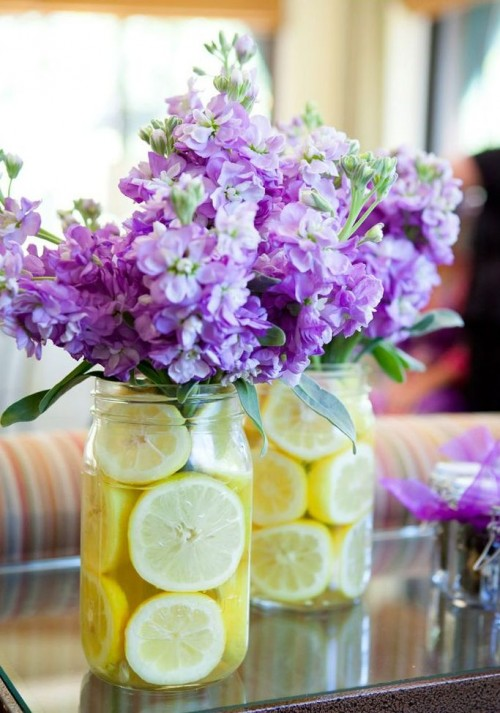 bright spring bridal shower centerpieces of purple blooms and lemon slices in jars