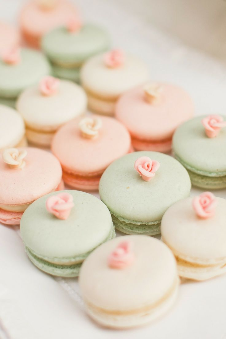 tender pastel spring macarons with sugar roses on top are nice sweets for a spring bridal shower