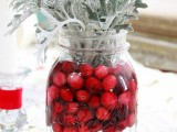 a jar with cranberries and pale millet is a cool idea of a centerpiece with a strong holiday feel
