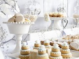 an all-white dessert table with cookies, cupcakes, macarons and other stuff will create a fairy-tale feel