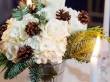 a simple and cute winter bridal shower centerpiece of white blooms, pinecones, evergreens in a large glass