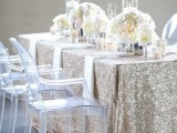 a glam winter bridal shower tablescape with a sequin tablecloth, white floral centerpieces and pillar candles