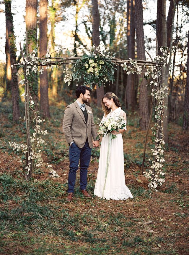 a lightweight woodland wedding arch of branches, with greenery, foliage and white blooms for a spring woodland wedding