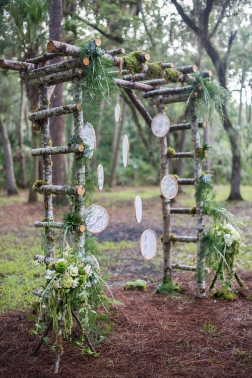 a woodland wedding arch of branches, with greenery, moss and lace embroidery hoops hanging down is a lovely idea with a natural feel