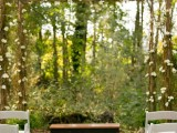an ethereal woodland wedding arch of branches and twigs, with some greenery and white blooms for a spring wedding
