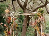 a woodland wedding arch of branches and sticks, with usual and bright fall leaves and succulents and air plants for a fall wedding