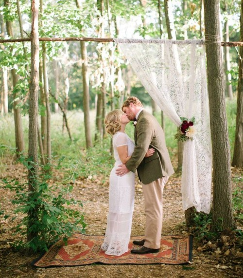 a simple wedding arch composed of a real tree and some branches, with naturally growing greenery and a boho rug, a lace curtain and blooms