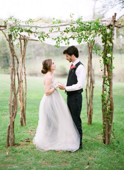 a gorgeous wedding chuppah of branches, with a lace curtain on top, some greenery and white blooms is ethereal and lovely