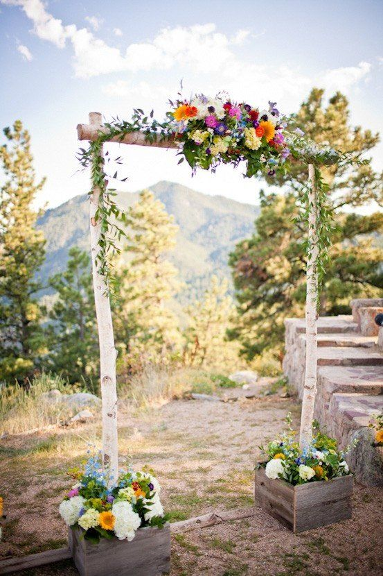 a rustic woodland wedding arch of birch branches, with greenery and bright blooms on top and in the crates is amazing