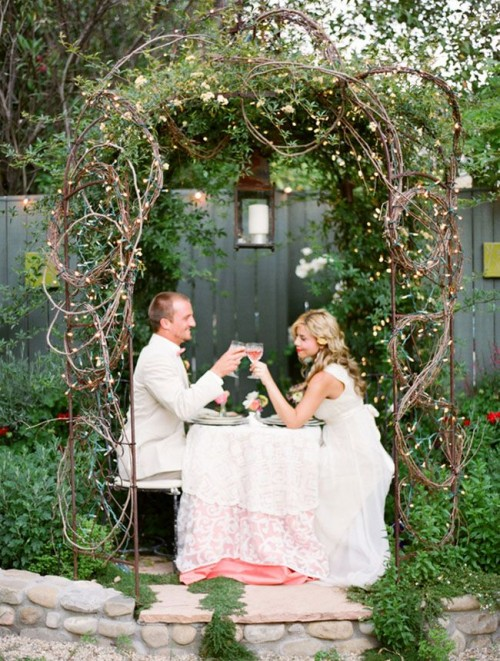 a fairy-tale woodland wedding arch of branches and vines, with greenery, neutral bloomsand leaves is romantic